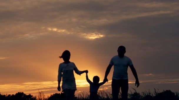 Šťastná rodina, běh v terénu při západu slunce. Silueta rodiny na letní večer. Pojetí lásky rodinné štěstí