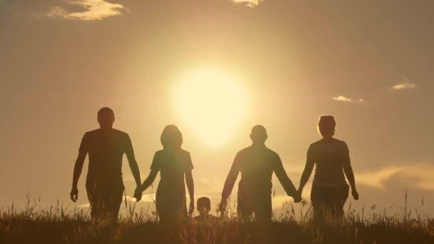 Mladá rodina s dětmi, běhá po poli, silueta při západu slunce