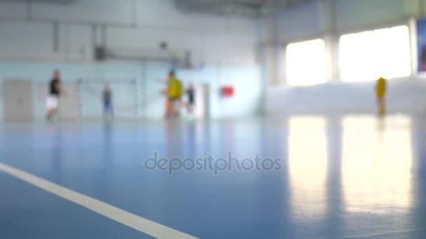 Labdarúgás futsal képzés a gyermekek számára. Teremfoci fiatal játékos-val egy futball-labda, sportcsarnok.