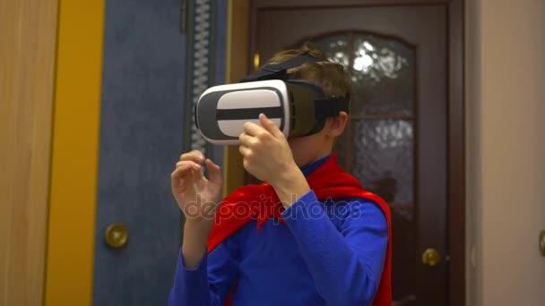 Chlapec, oblečený jako superhrdina v virtuální realita brýle hraje doma