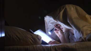 A child reads a book under blankets with a flashlight at night. Enthusiastic boy