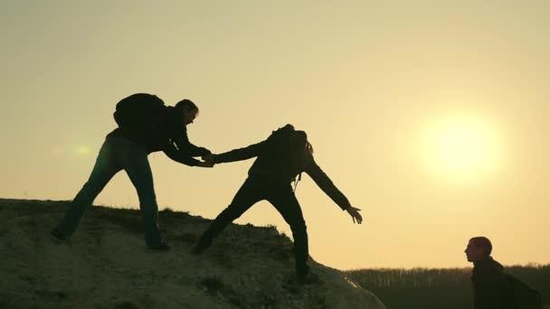 Silhouetten von Touristen, die vor dem Hintergrund eines Sonnenuntergangs die Klippen erklimmen und sich gegenseitig helfen. Hilfe in den Bergen und Teamarbeit beim Wandern. Teamwork-Konzept.