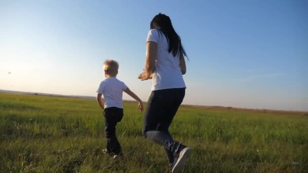 Mladá matka si hraje s dítětem na ulici. Žena běží za malým veselým synem. Šťastná rodina se baví venku.