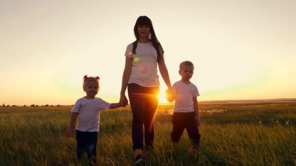 Egy fiatal anya sétál két kisgyerekkel a parkban a fűben. Egy boldog család sétál a szabadban a lenyugvó napon..