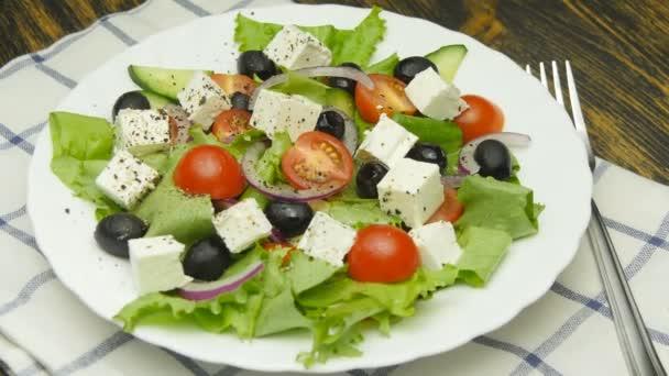 Řecký salát s čerstvou zeleninou, feta sýrem a černými olivami otočit