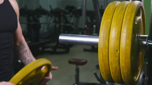 Bodybuilder guy prepare to do exercises with barbell in a gym, keep barbell plate in hands
