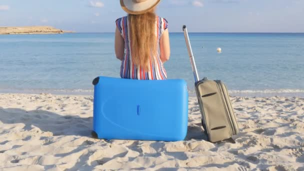 Young woman traveler sits on the beach with a suitcase