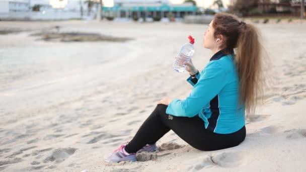 Nádherné fitness žena sedí a odpočinek u moře