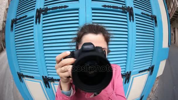 Legrační mladá žena fotograf s kamerou. Rybí oko