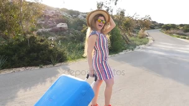 Happy Woman walking with suitcase on road
