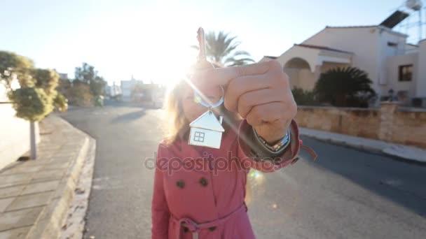 Eine Frau mit einem Schlüssel von einem neuen Haus