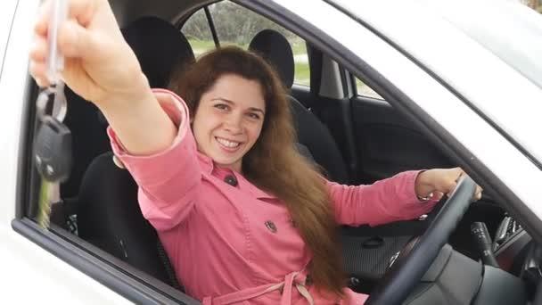 Šťastná mladá řidička drží klíče od auta řídí její nové auto
