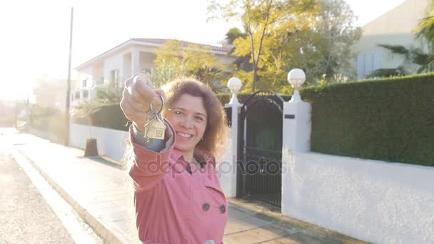 Mladá žena v ruce drží klíče od nového domu