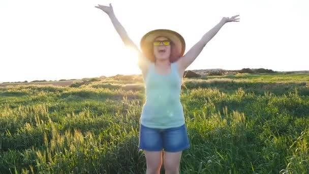 glückliche junge Frau mit Hut genießt den Sommer auf der grünen Wiese bei Sonnenuntergang
