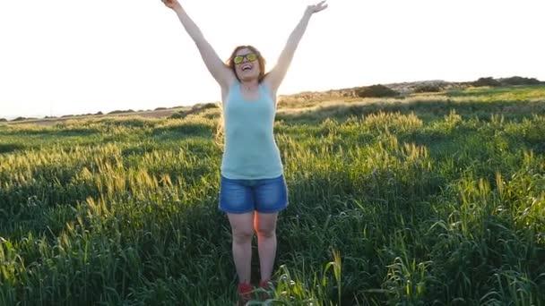 Šťastná mladá žena v klobouku těší letní v zeleném poli při západu slunce