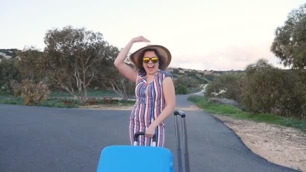 glückliche junge Frau im Urlaub mit Hut und Koffer