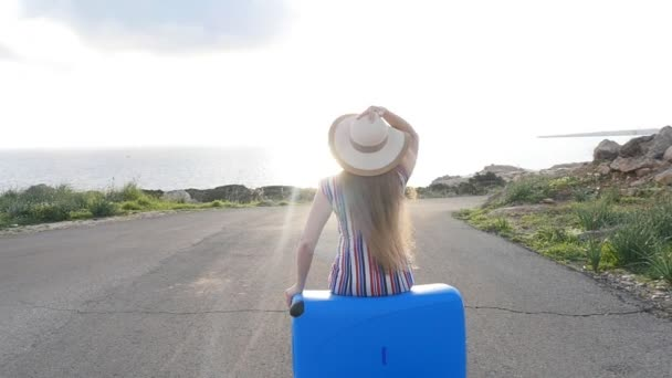 Traveler woman sits on suitcase and looks away on road