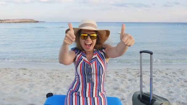 Šťastná mladá žena sedí na kufru ukazuje palec