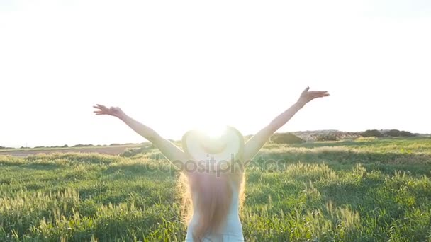 Woman with arms outstretched in a field
