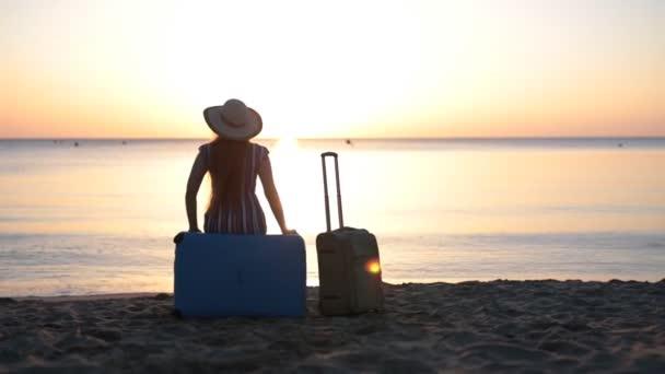 Mladá žena sedí na kufru u moře