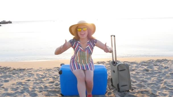 glückliche junge Frau im Urlaub mit einem Koffer, der Daumen nach oben zeigt