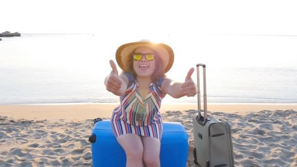 Šťastná mladá žena s kufrem palce nezobrazovaly na dovolenou