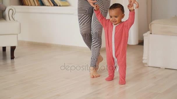 Máma učí syna chodit. Smíšené rasy baby