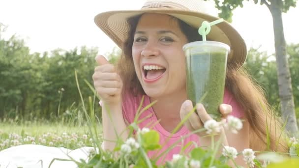 Junge Frau trinkt gesunde Entgiftung im Freien
