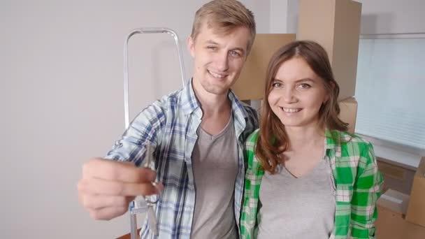 Mladý šťastný pár s krabicemi a hospodářství ploché klíče