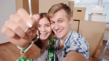 Couple showing keys to new home and selfie
