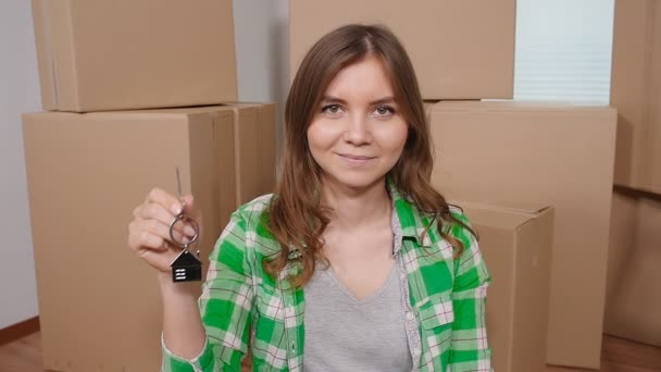 Happy young woman holding key house shaped keychain.