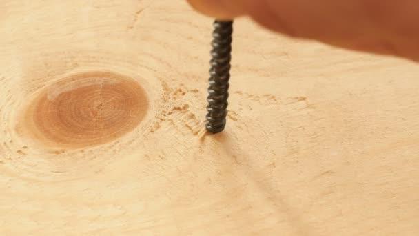 Šroubování šroubu v dřevěném prkénku