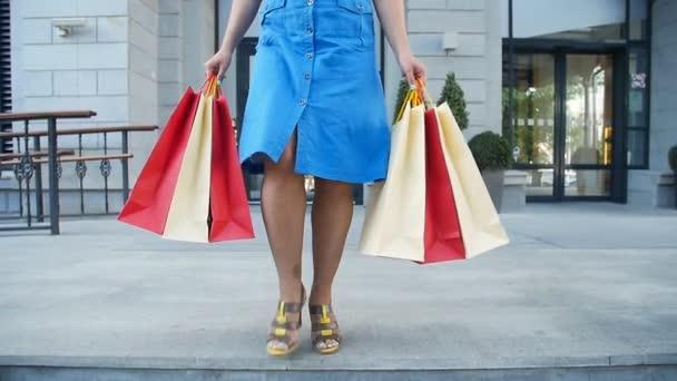 Mladá šťastná žena s nákupníma taškama z obchodu