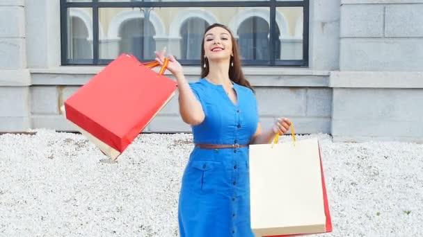 mosolygó fiatal nő, bevásárló táskák