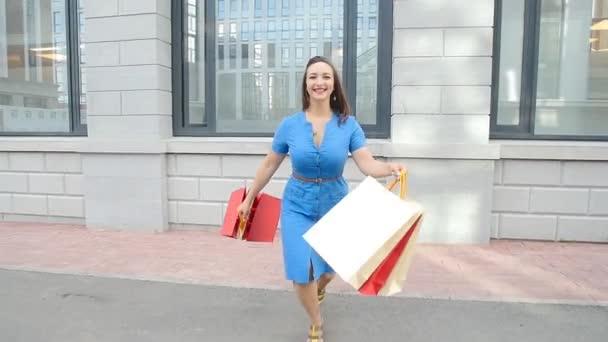 fiatal nő fut a bevásárló szatyrok kezébe a szabadban