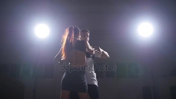 Bailarines de bachata en el cuarto oscuro iluminado — Vídeo de stock ...