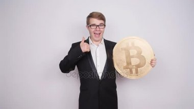 Business man holding big bitcoin in his hands. Cryptocurrency, people, technology, money and future concept