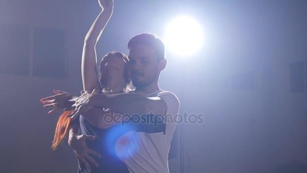 A fiatal pár tánc latin zene. Bachata, merengue, salsa. Sötét szobában