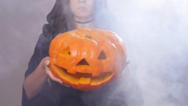 Žena čarodějnice stojí s dýně v kouři
