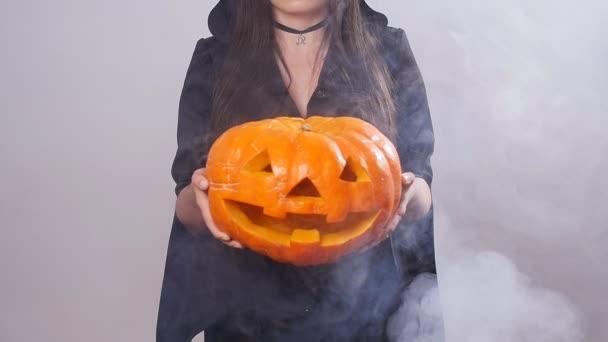 Frau Hexe steht mit dem Kürbis in Rauch