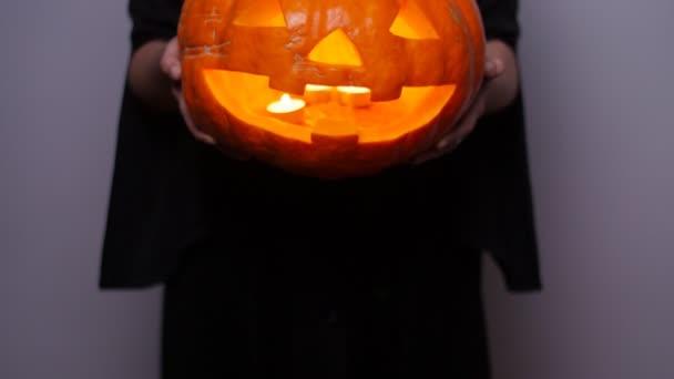 Hexe mit einem geschnitzten Kürbis. Halloween-Konzept