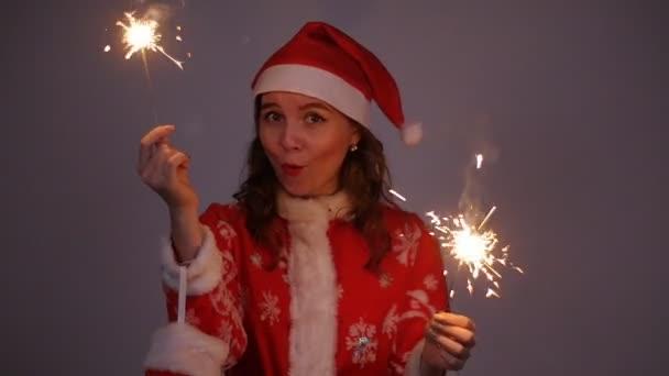Fiatal nő Mikulás piros karácsony vagy újév kabát és kalap gazdaság csillagszóró