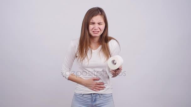 Mladá žena trpí bolest žaludku na šedém pozadí