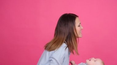 Young happy woman hugging her little son on a pink background