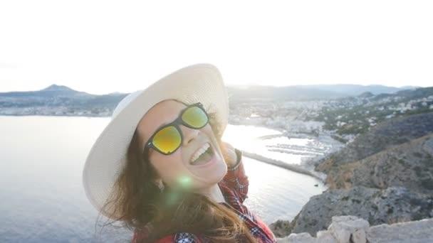 Šťastná žena cestovatele v sluneční brýle dělá selfie s mořem a výhledem na moře