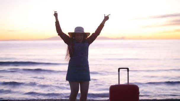 Glückliche Touristin mit Koffer am Meer bei Sonnenuntergang