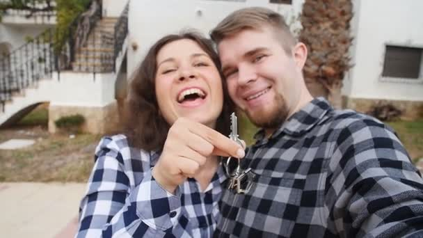 New homeowners with key selfie. Real estate, new house or apartment and people concept