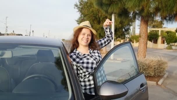Woman driver showing car keys smiling happy in her new car