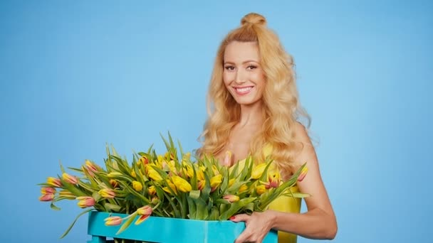 Young blonde woman with tulips on blue background