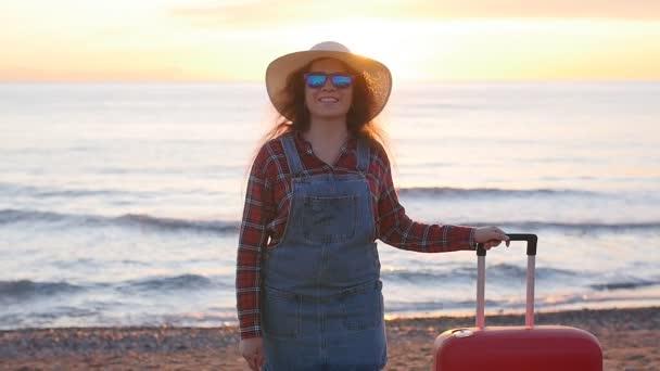 junge Reisende mit einem Koffer am Strand bei Sonnenuntergang